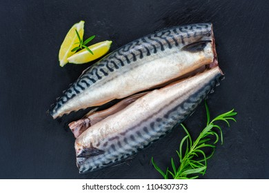Two raw mackerels on black background - top view