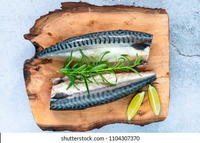 Two raw mackerels on wooden board - top view