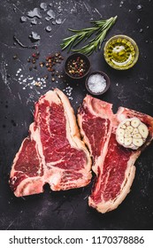Two raw marbled meat steak T-bone, spices, herbs, stone background. Beef T-bone steak, ready for cooking. Top view. Ingredients for meat roasting. T-bone steak. Meat steak concept. Close-up. Barbecue