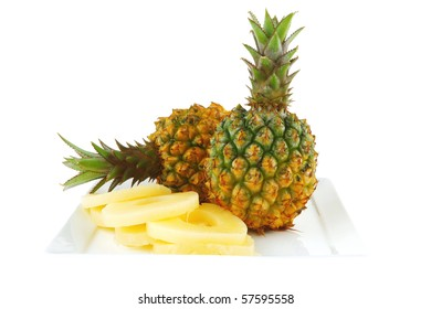 two raw pineapples on plate over white