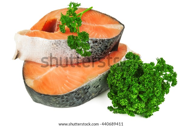 two raw salmon steaks with parsley leaves on white background