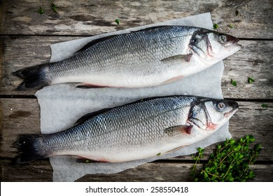 two raw sea bass with fresh thyme on wooden rustic table