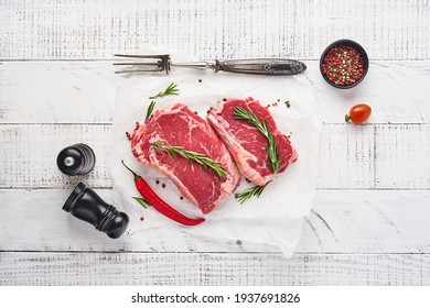 Two raw steak New York with rosemary and spices on a piece of parchment paper on old white wooden background. Top view. Mock up.