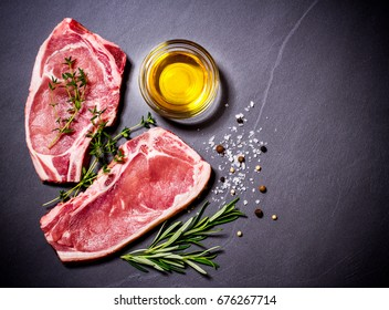 Two raw veal chops with ingredients, top view