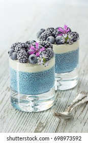 Two Raw Vegan Blue Spirulina Chia Puddings Topped with Whipped Coconut Cream and Frozen Blackberries and Blueberries