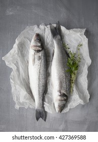 Two raw whole fish sea bass on white paper on grey shabby background with fresh herbs