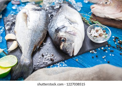 Two ready to cook dorado fish with herbs, lemon and olive oil on stone slate board. Dorado fish on blue boards.