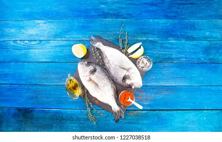 Two ready to cook raw bream fish with herbs, lemon and olive oil on stone slate board. Dorado fish on blue boards. With copy space. Top view