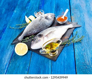 Two ready to cook raw bream fish with herbs, lemon and olive oil on stone slate board. Dorado fish on blue boards. With copy space
