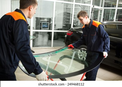 Two Real Mechanics changing the broken windshield of black car in Auto Repair Shop