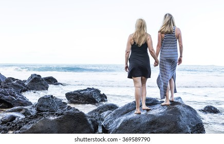 Two recently engaged women dressed in beach attire, holding hands on a rock by the ocean.