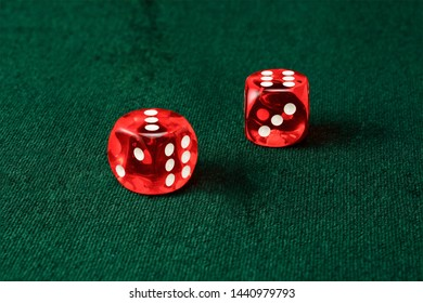 Two red acrylic transparent dice for games. Gambling translucent dice isolated in a white background, macro close up high resolution..
