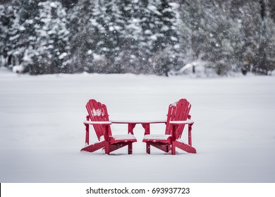 Two Red Algonquin Adirondack chairs on snow covered lake in winter