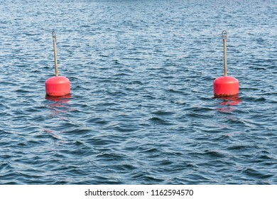 Two red anchor buoys in blue water