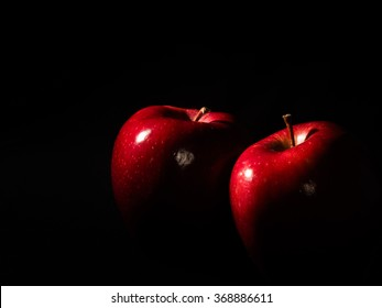 Two red apple on black background
