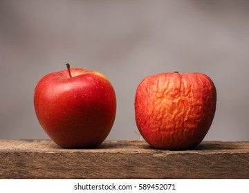 Two red apples on a rustic wooden table