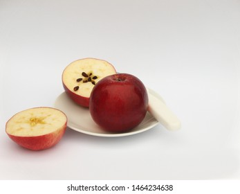 Two red apples, one whole apple, the other one sliced into two halves, on the small plate, isolated on the white background.