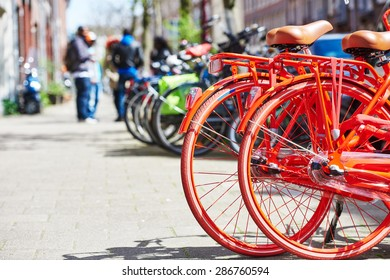 Two red bicycle on the city street near hotel in Amsterdam