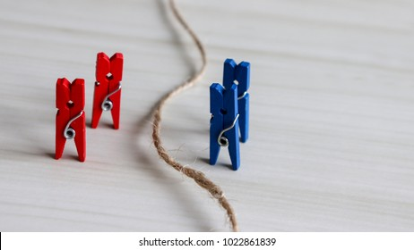 Two red laundrytongsand two blue laundry tongs. Gender discrimination concept