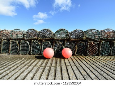Two red buoys against lobster and crab creels in a row on the harbour pier in the fishing village of Anstruther in the Kingdom of Fife near St. Andrews, Scotland.