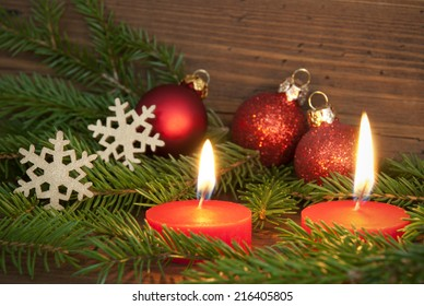 Two Red Burning Candles with Christmas or Winter Decoration as Winter, Christmas or Advent Background with Copy Space