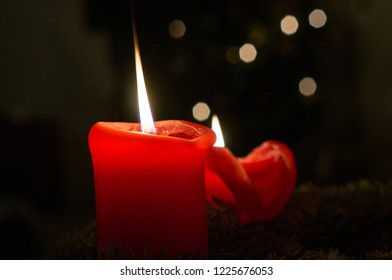 Two Red Candles with Bokeh Balls from a Christmas Tree