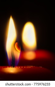 two red candles glow in the dark