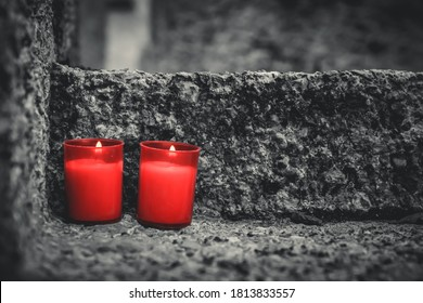 Two red candles on a grave. Lanterns on a tombstone at All Saints' Day in a cemetery. Shallow depth of field. Religion, funeral, mourning concept.