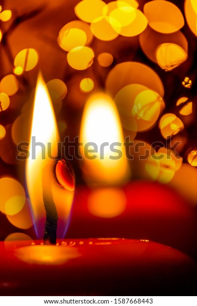 Two red candles shine with warm light. Festive bokeh sparkles in the background. Concept: festive lighting