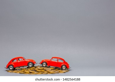 Two red car figurines placed on top of a big heap of golden coins, on gray background.