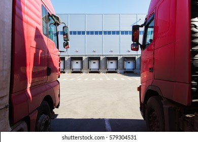 Two red cargo truck standing in the parking lot in front of loading docks modern warehouse