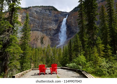Two red chairs at a bottom of Takakkaw falls on a sunny afternoon. Takakkaw Falls is a waterfall located in Yoho National Park, near Field, British Columbia in Canada.