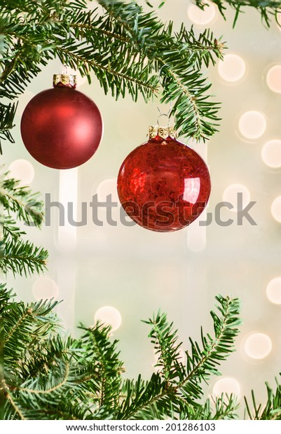 Two red Christmas ornaments hung from a Christmas tree with lights and window in the background. Shot with copy space.
