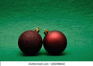 Two red Christmas tree baubles on a green background
