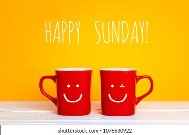 Two red coffee mugs with a smiling faces on a yellow background with the phrase Happy sunday. Happy coffee mugs.