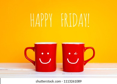 Two red coffee mugs with a smiling faces on a yellow background with with the phrase Happy friday. Happy coffee mugs.