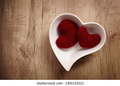 Two red crochet hearts in a bowl on a wooden table