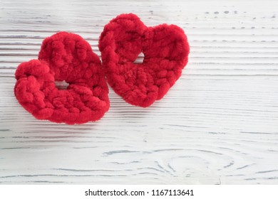 Two red crocheted hearts on wooden background. Vintage style. Photo of crochet, knitted colorful elements for Romantic Christmas or Valentines Day holidays.