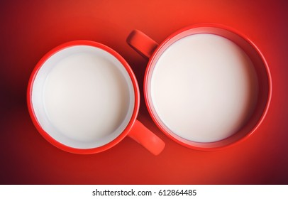 Two red cups with milk on the red table.