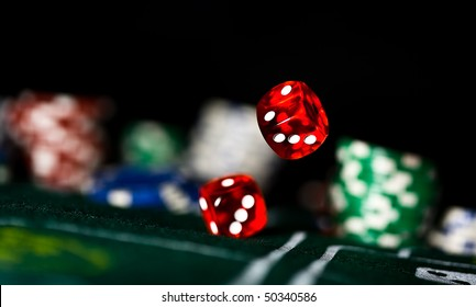 two red dice rolling on felt