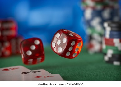 Two red dice rotates in the air, casino chips, cards on green felt