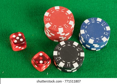 two red dices and different chips on green background. gambling and betting addiction concept