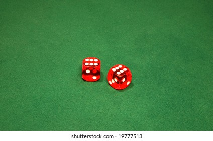 Two red dices on the green table in casino