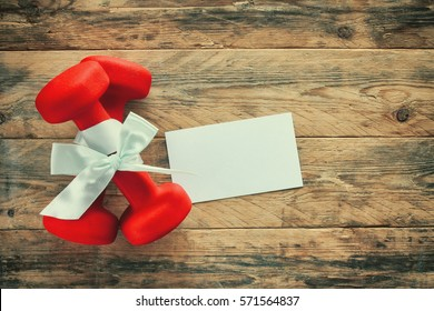 two red dumbbell with gift bow, blank paper label on a wooden planks, sport holiday concept