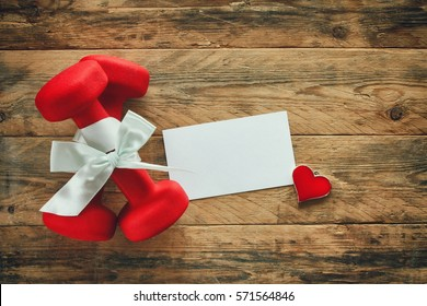 two red dumbbell with a gift bow and blank paper tag, heart on wooden planks, sport holiday concept