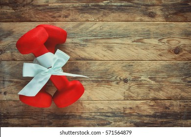 two red dumbbell with a gift bow on a wooden plank floor, sport holiday concept