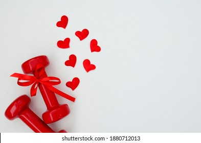 Two red dumbbells and hearts on a white background with copy space. Concept of Valentines day, healthy lifestyle, giving gifts, love of sports, shopping