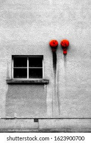 Two red emergency bells on a grey concrete wall and a window