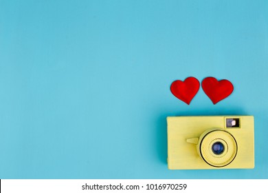 Two red fabric hearts and yellow vintage camera on blue background, copy space. Valentine, love, romantic, wedding photography, I love photography concept