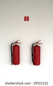 two red fire extinguishers on white wall